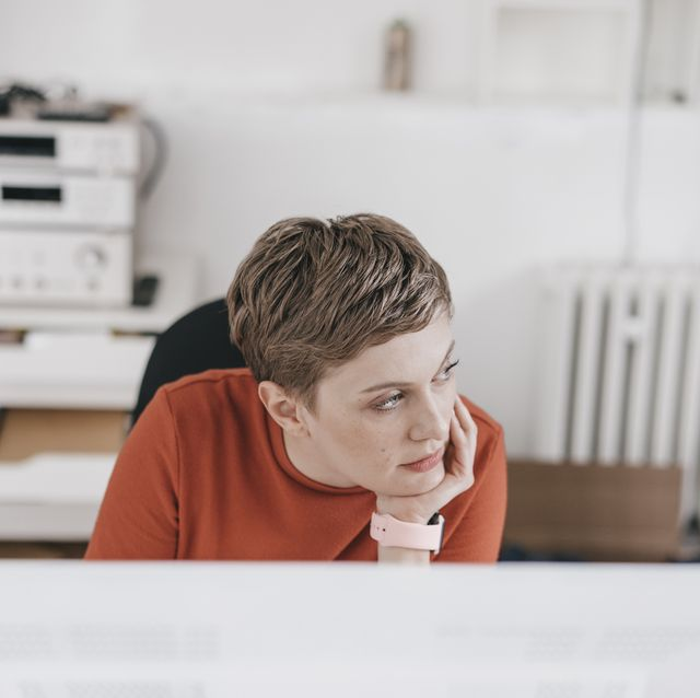 woman at desk in office thinking