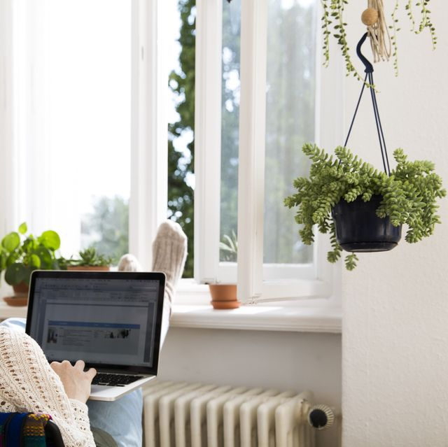 woman at home using laptop at the window