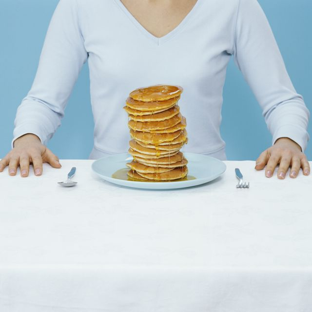 woman at table with plate of pancakes, mid section digital composite
