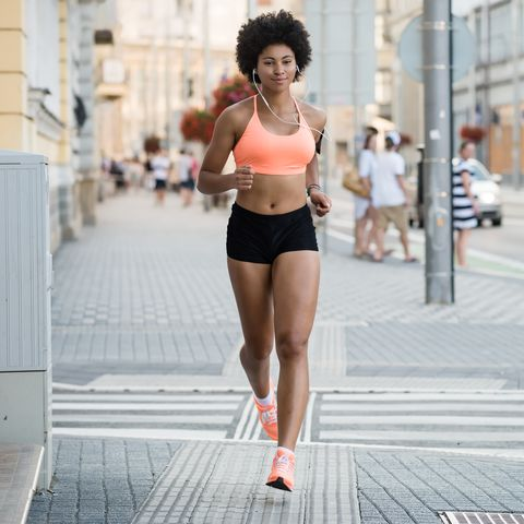 woman athlete running on city street