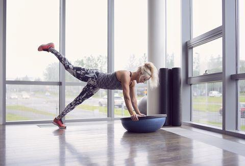 Woman balancing on BOSU ball in gym