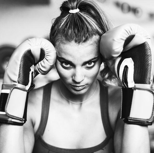 Mujer practicando boxeo en el gimnasio con los guantes puestos.