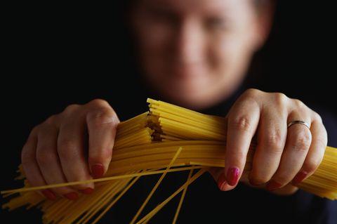 Woman Breaking Spaghetti