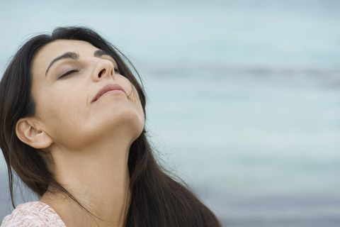 Woman breathing outdoors with head back and eyes closed