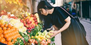 Woman Buying Fruits on Street Market