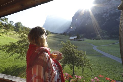 Woman enjoys view from mountain chalet veranda