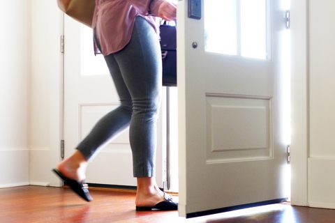 Woman carrying walking out from door.