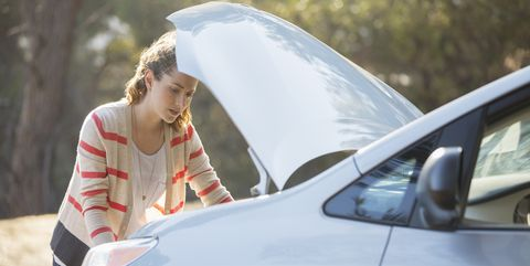 Woman checking car engine at roadside