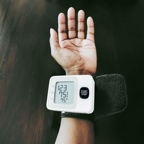 woman checks blood pressure at home