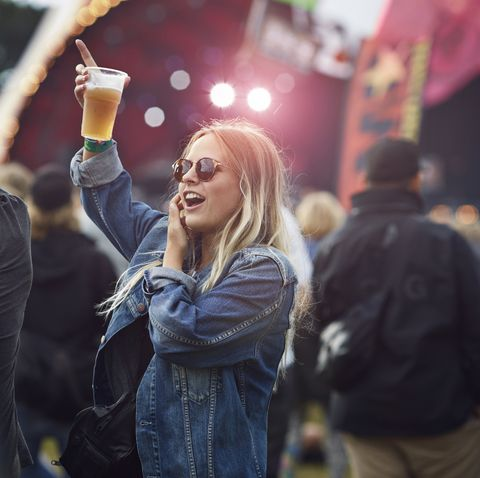 woman cheering with beer at concert