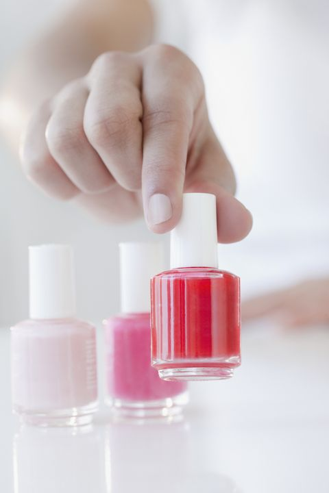 Woman choosing red fingernail polish bottle