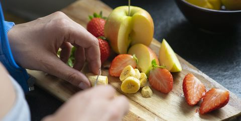 woman chopping fruits in her kitchen, close up