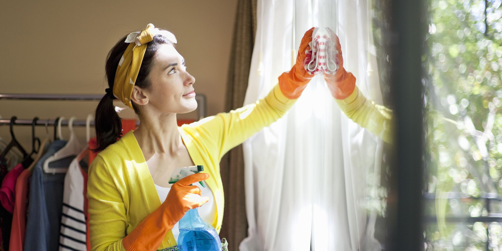 woman cleaning the windows of her apartment