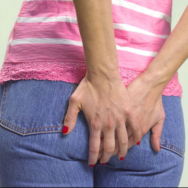 woman clutching bottom with problems