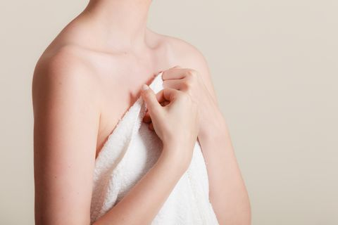 woman covering breast under towel