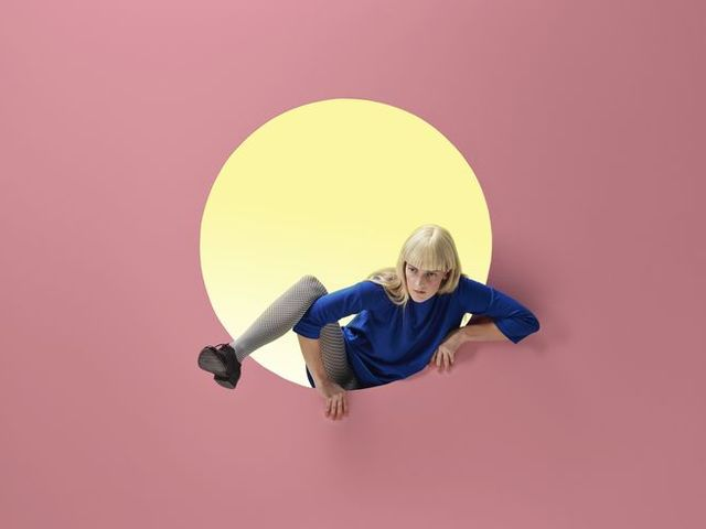 Woman crawling out of round opening in coloured wall