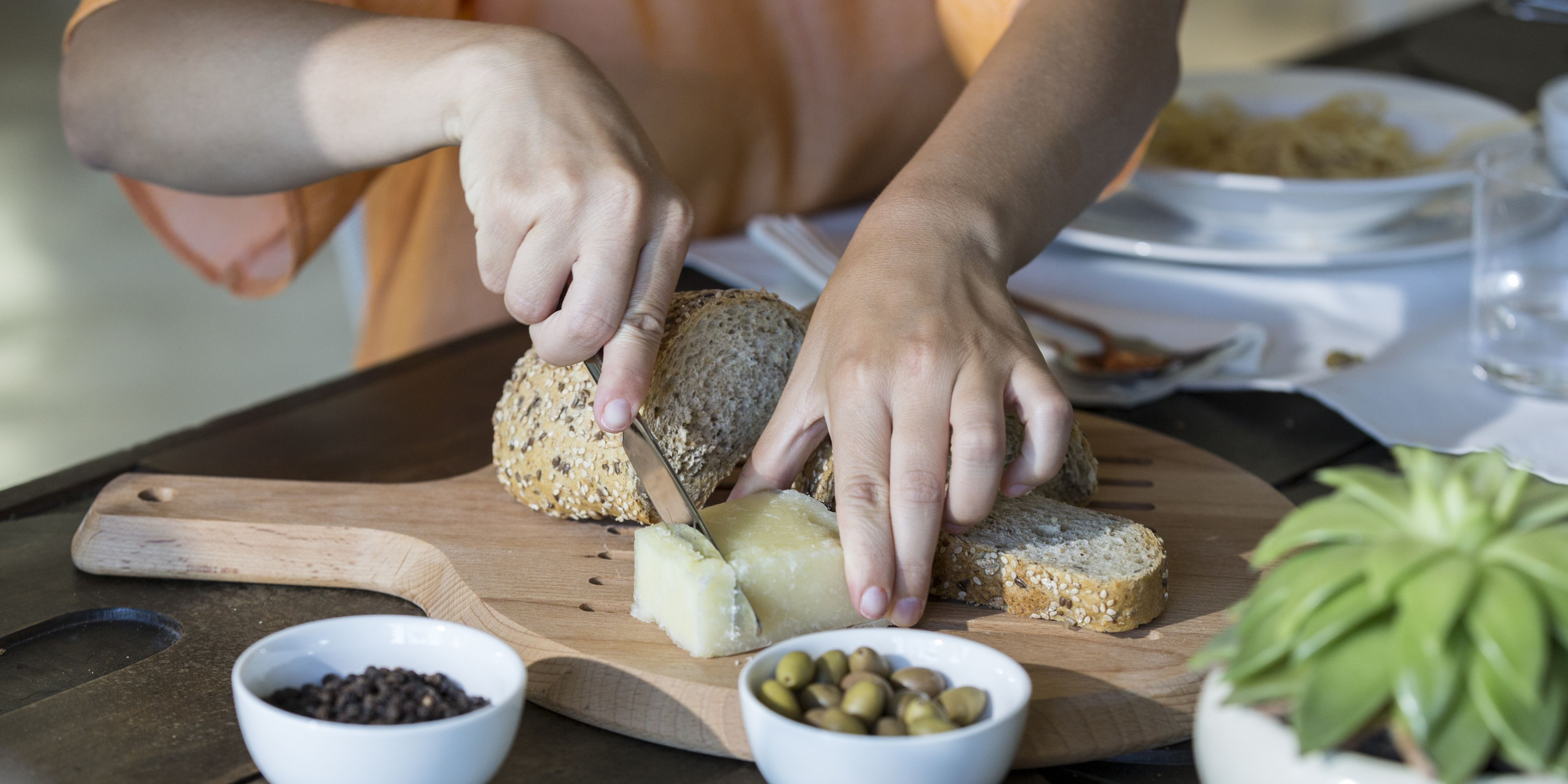 Woman cutting cheese and bread on chopping board