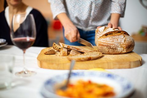 woman cutting loaf of bread on dining table