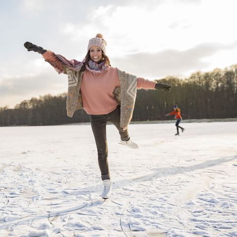 woman dancing with ice skates on frozen lake with friends