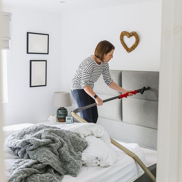 woman deep cleaning her bedroom