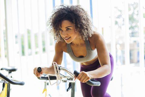 Mulher fazendo exercícios cardiovasculares em uma bicicleta estacionária no ginásio