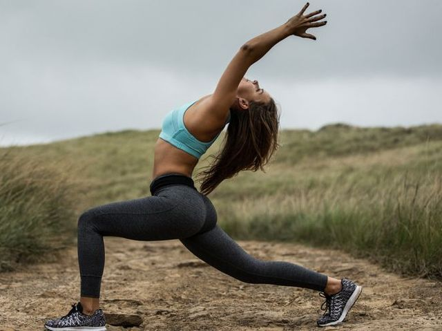 Woman doing high crescent lunge on dirt road