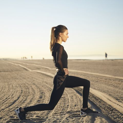 Woman doing lunges on beach