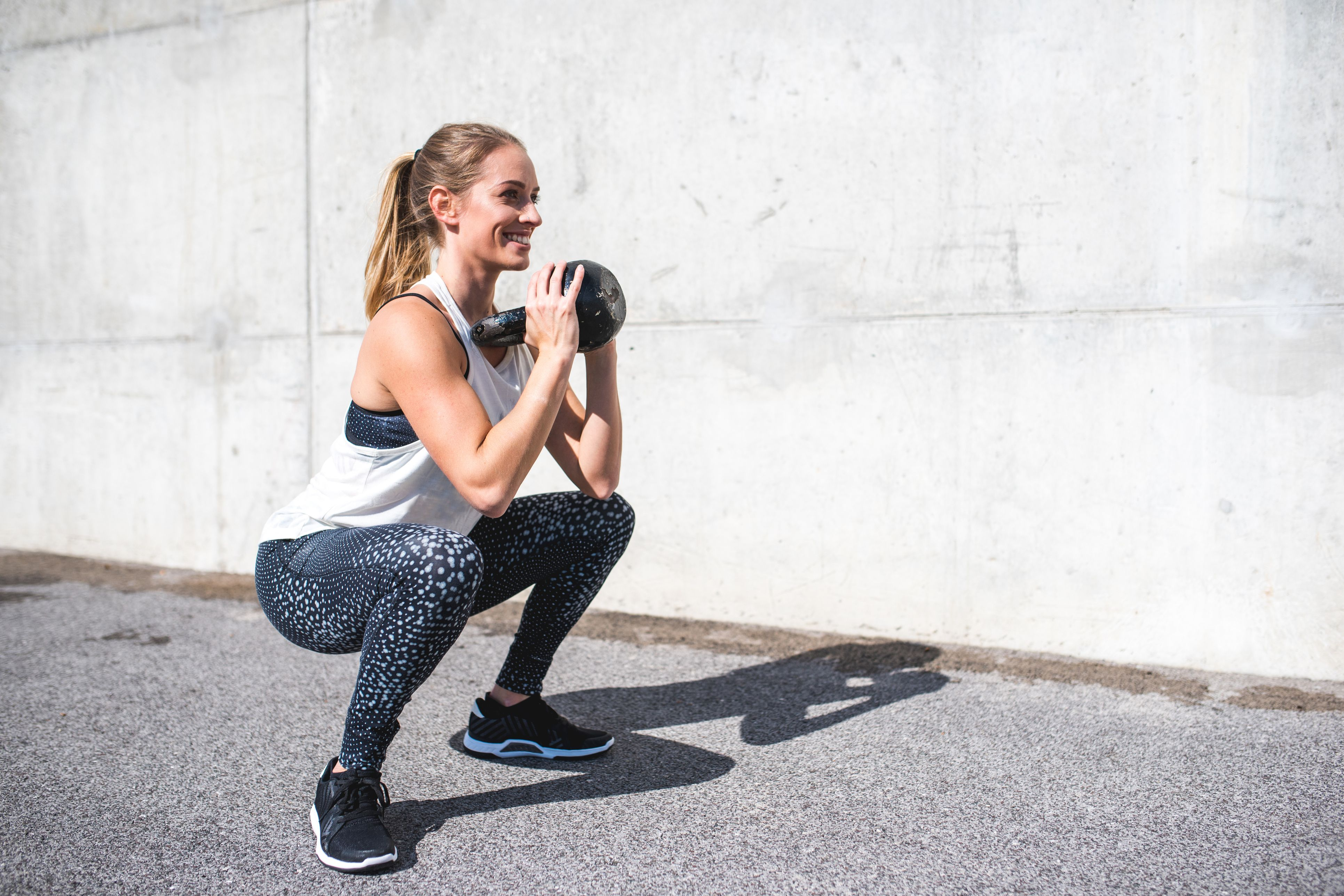 Woman doing squats with a kettlebell