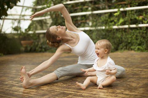 Woman doing yoga exercise while baby having fun