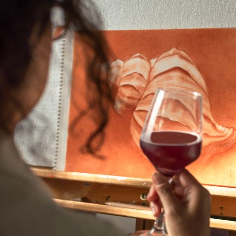 woman drinking a glass of wine to celebrate that she has finished her painting artist contemplating his finished work