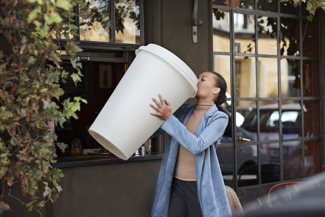 woman drinking coffee from large disposable cup at take away counter of cafe