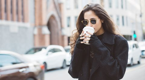 woman drinking coffee in the city