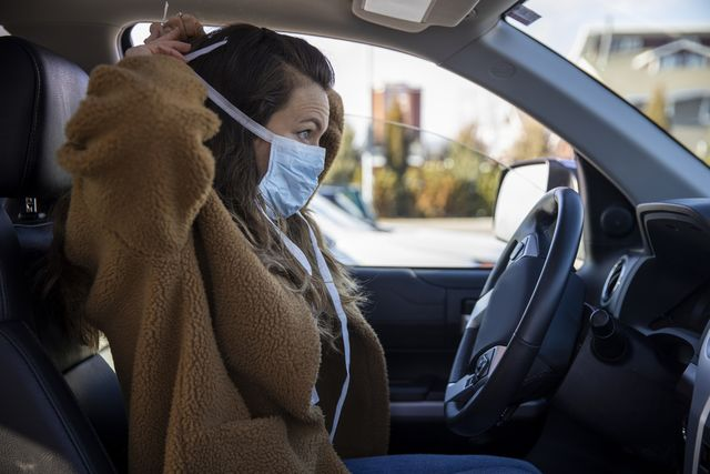 a woman driving her vehicle wearing latex gloves and a mask during the covid 19 pandemic