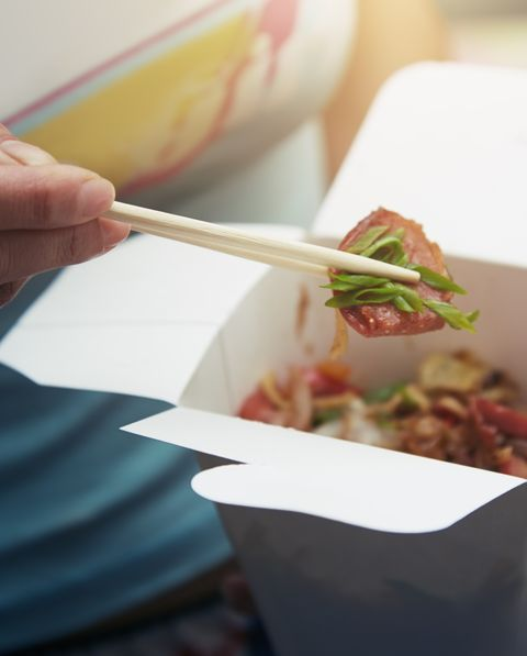 woman eating asian fast food from a cardboard box