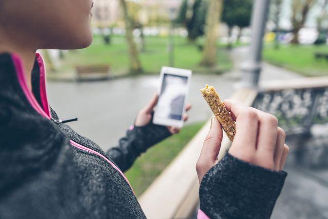 una corredora con una barrita de cereal y un móvil