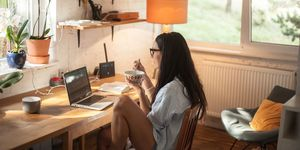 Woman Eating Food While Using Laptop On Table At Home