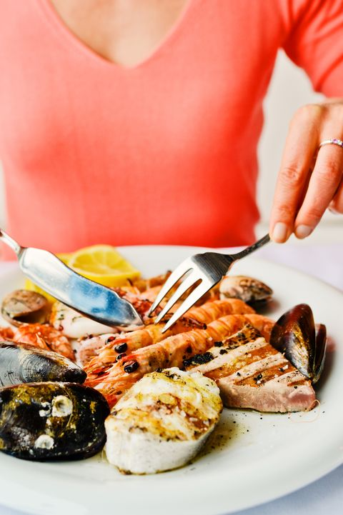 woman eating grilled seafood in a restaurant