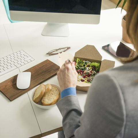 woman eating salad for lunch at her desk