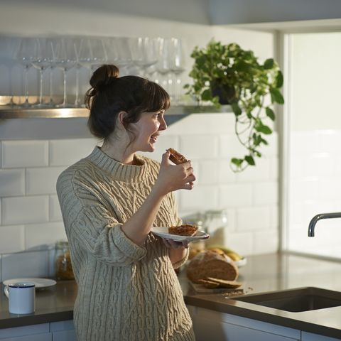 woman eating toast at breakfast and looking out of kitchen window