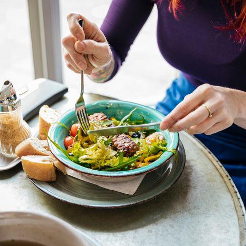 woman eating vegan dish in cafe