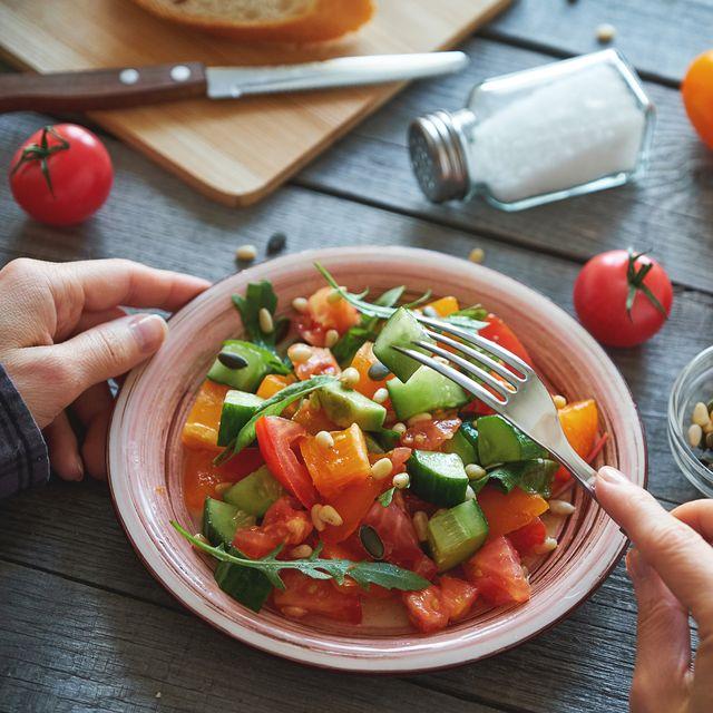 a woman eats a vegetarian vegetable salad