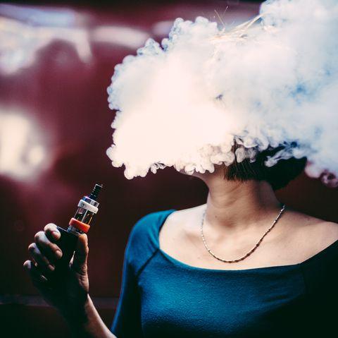 Woman Emitting Smoke While Smoking At Home