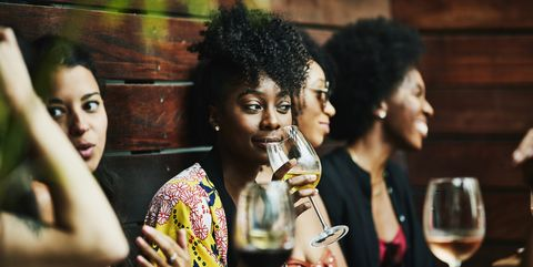 Woman enjoying drink with friends at poolside bar