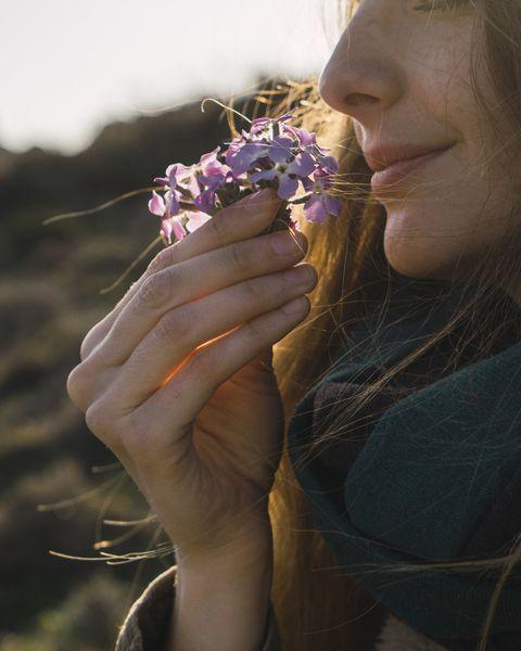 Woman enjoying fragrance of a flower