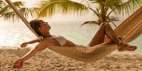 woman enjoying little rain while relaxing in a beach hammock