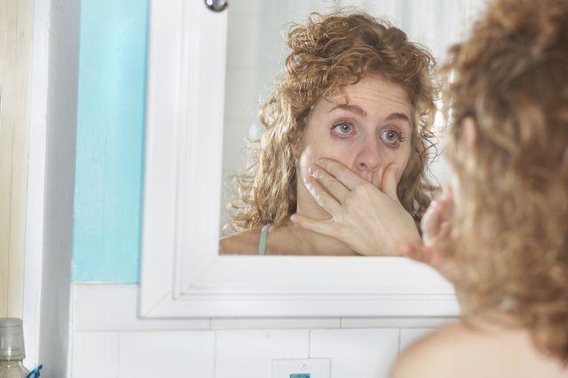 woman examining her eyes
