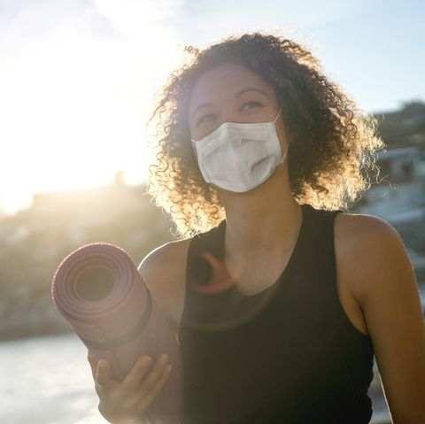 woman exercising at the beach wearing a facemask and holding a yoga mat