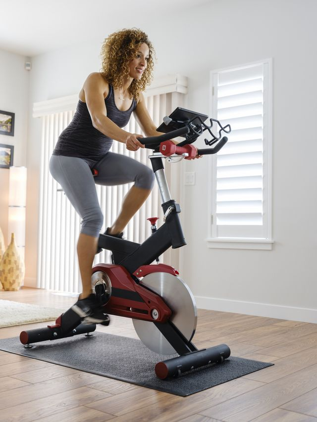 woman exercising on spin bike in home