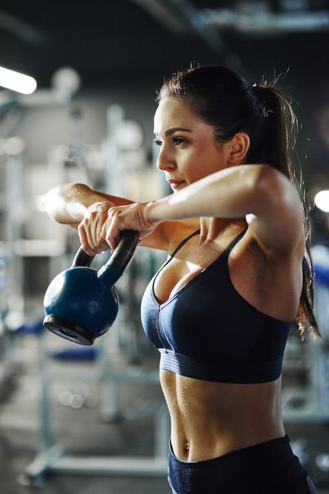 woman exercising with a kettlebell in gym