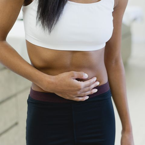woman experiencing abdominal pain, mid section